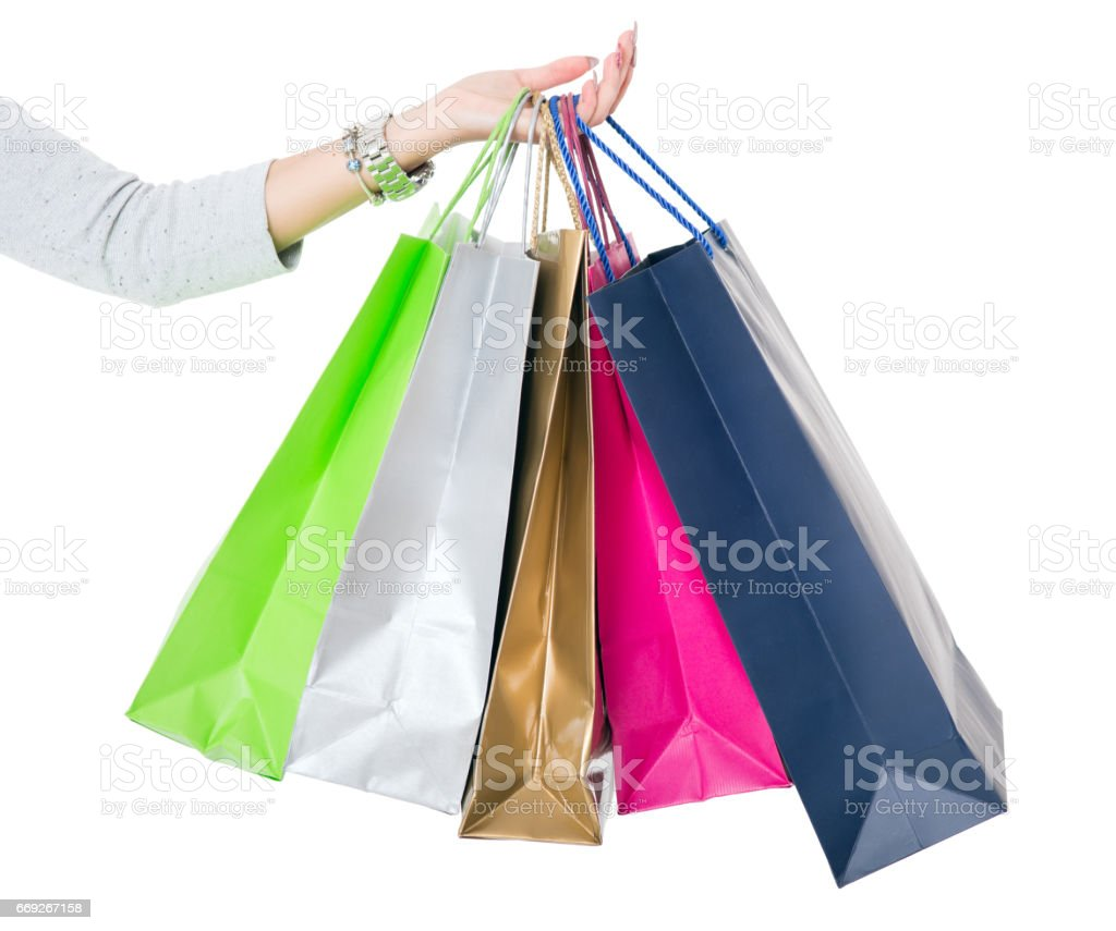 Shopping Bags. Female hand holding colorful shopping bags on white'n stock photo
