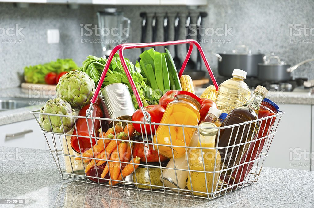 Shopping basket filled with groceries shot on kitchen counter top stock photo