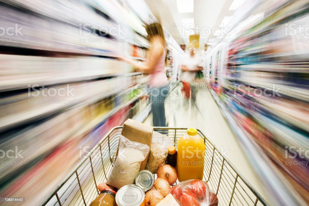 Shopping cart approaches woman in aisle. Motion blur. royalty-free stock photo