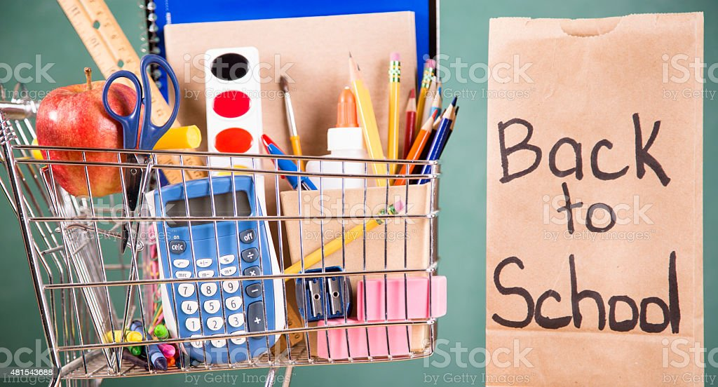 Shopping cart filled with back to school supplies. stock photo