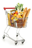 Shopping cart filled with variety of groceries on white backdrop