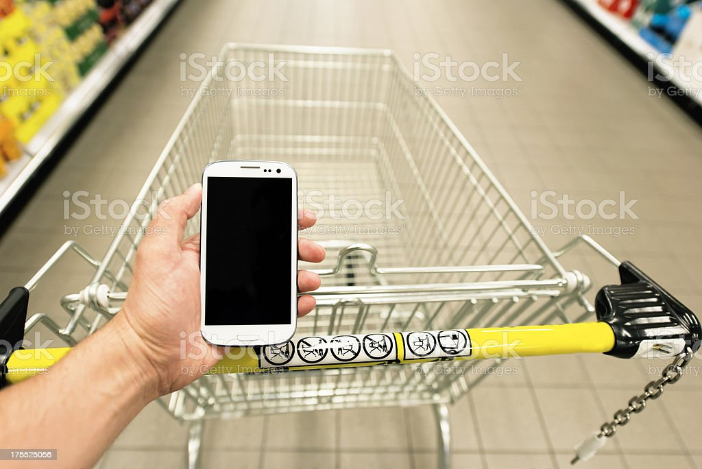 Shopping cart in the supermarket and a smart phone royalty-free stock photo