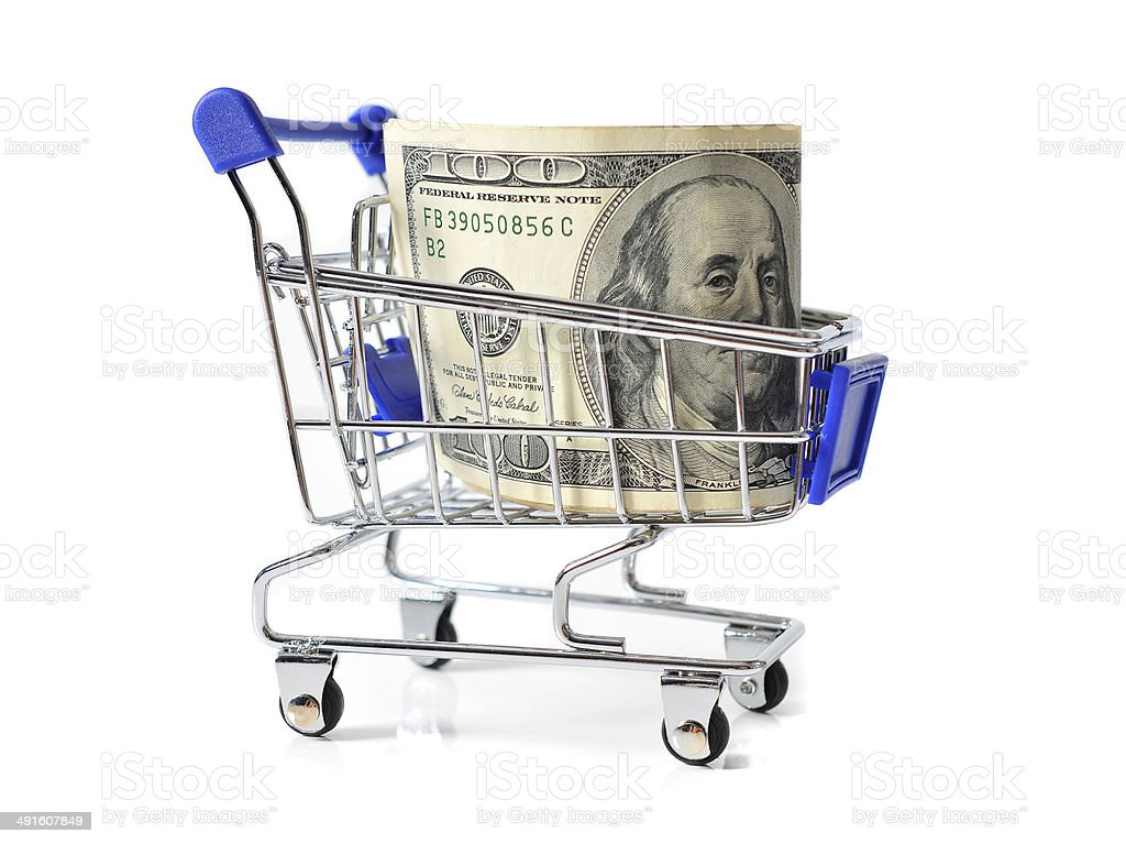 Shopping cart loaded with 100 dollar banknotes on isolated background stock photo