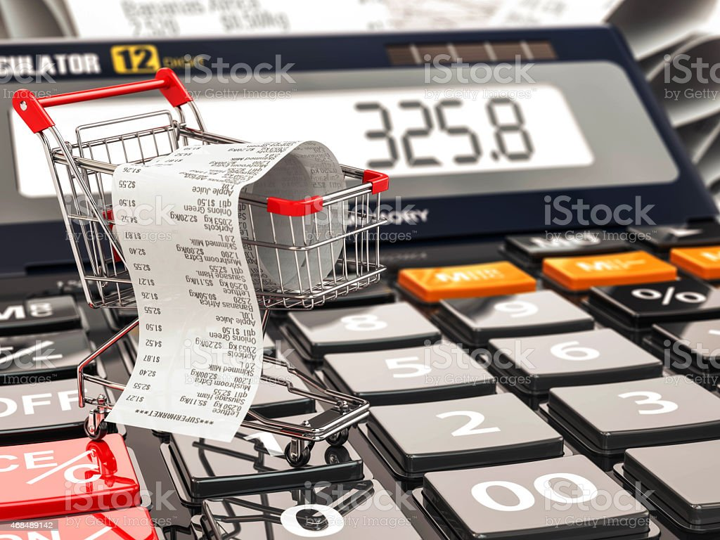 Shopping cart on calculator and receipt. Home budget or consumer stock photo