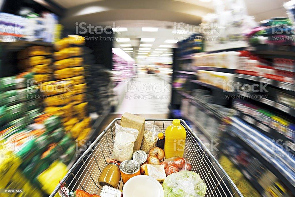 Shopping cart races down aisle. Fisheye lens and motion blur. stock photo