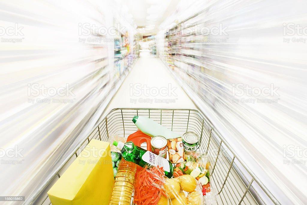 Shopping cart races through blurred, white shelves stock photo