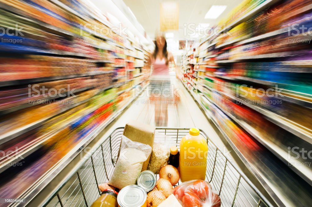Shopping cart races through store with rainbow motion blur surrounding royalty-free stock photo