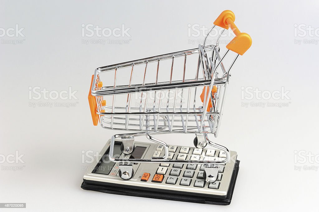 Shopping cart situated on calculator on gray stock photo