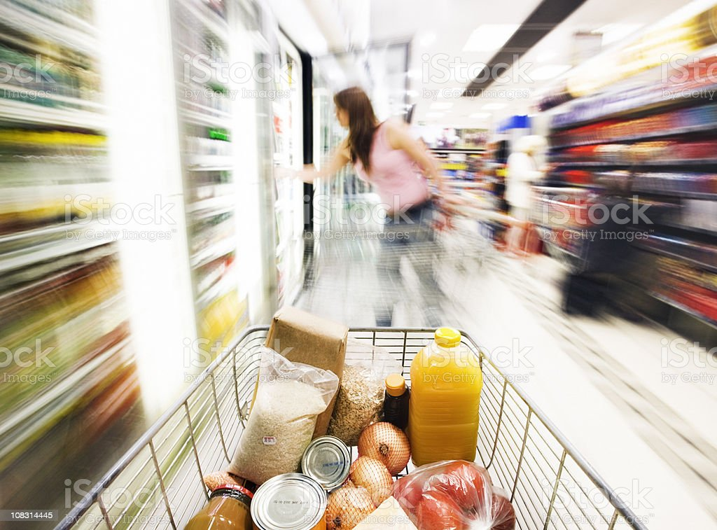Shopping cart speeds towards chiller cabinet with motion blur stock photo