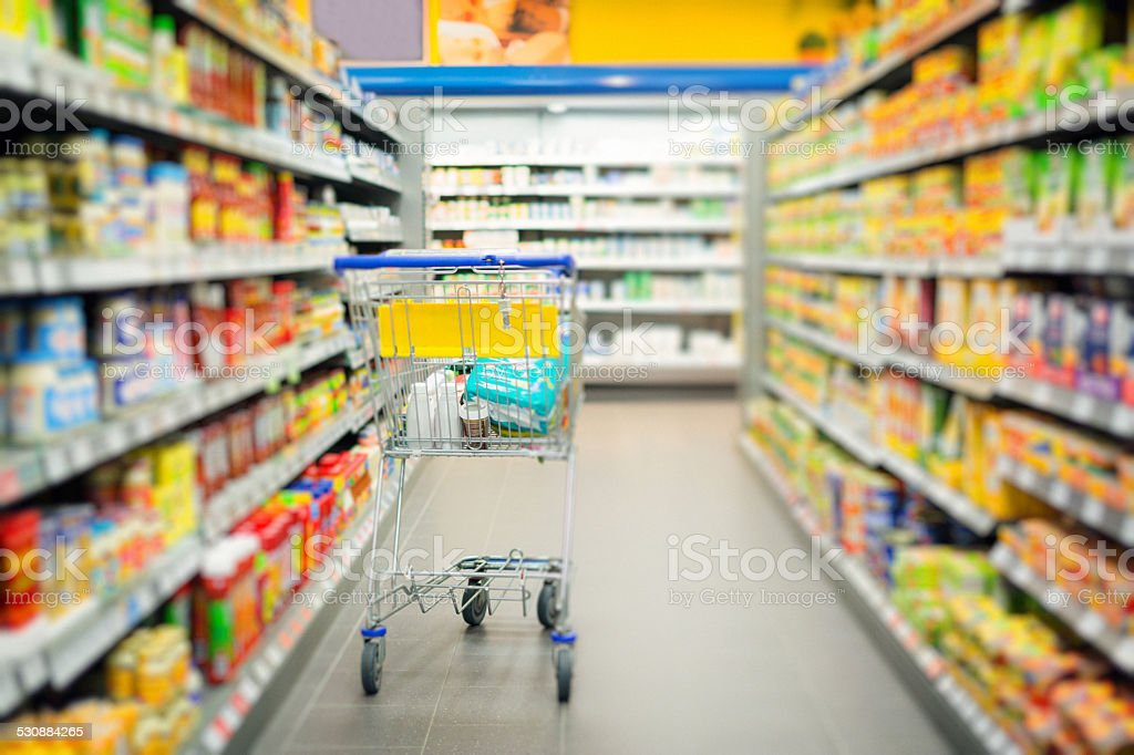shopping cart standing in a supermarket's aisle stock photo