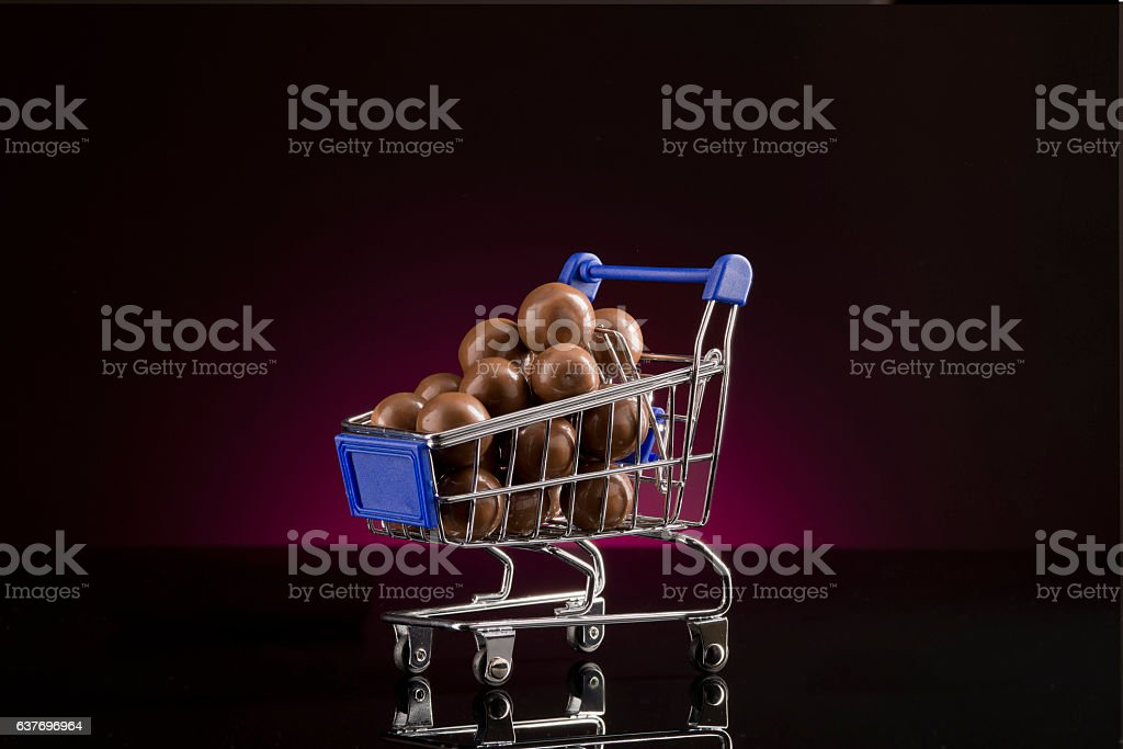 Shopping Cart with big chocolate candy stock photo