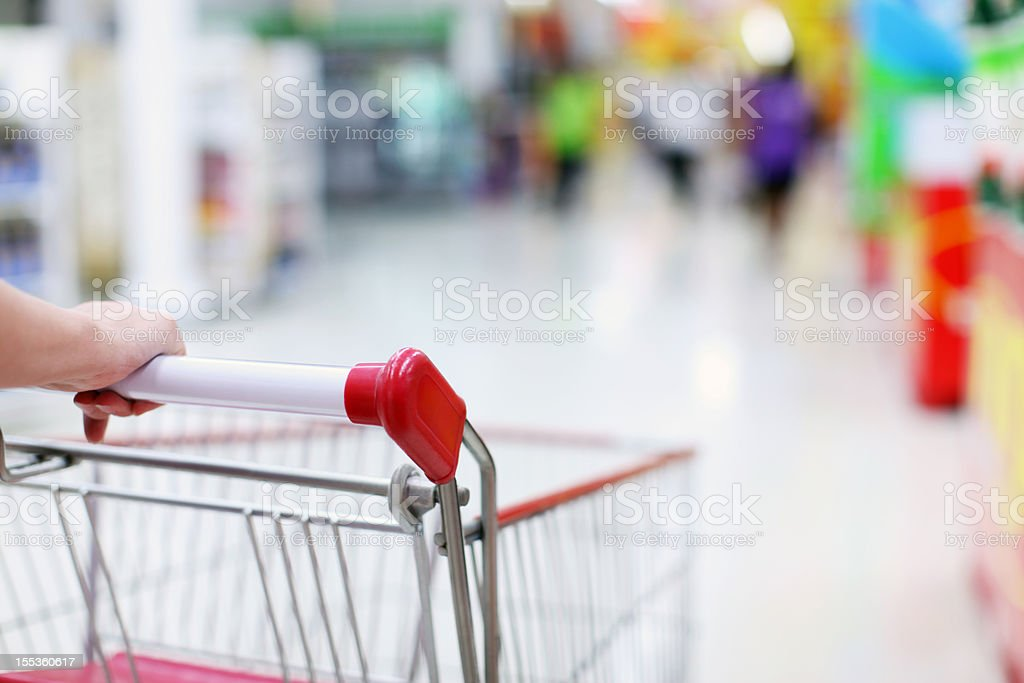 Shopping cart with blurred people and store stock photo