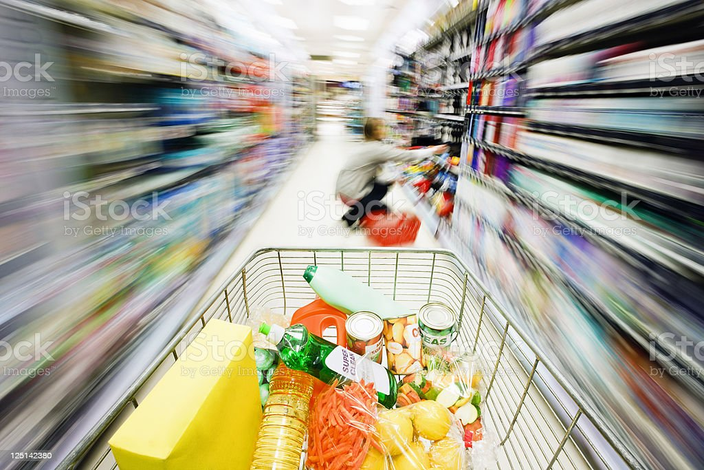 Shopping cart's speed creates rainbow motion blur in supermarket aisle stock photo