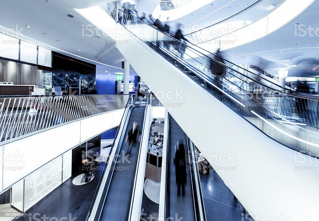 Shopping centre with moving people on escalators stock photo