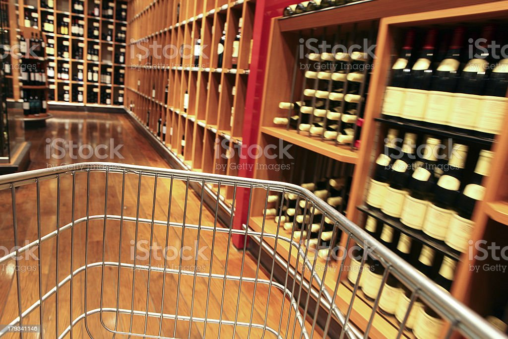 Shopping: choosing the right wine bottles with empty cart royalty-free stock photo