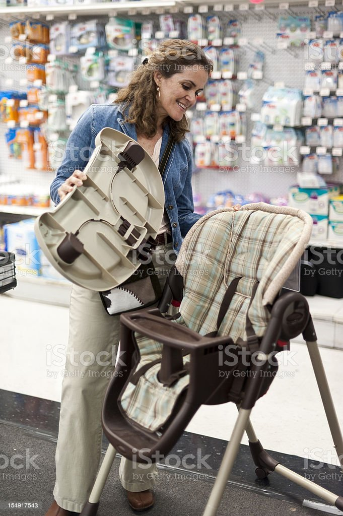 Shopping for a new baby high chair royalty-free stock photo