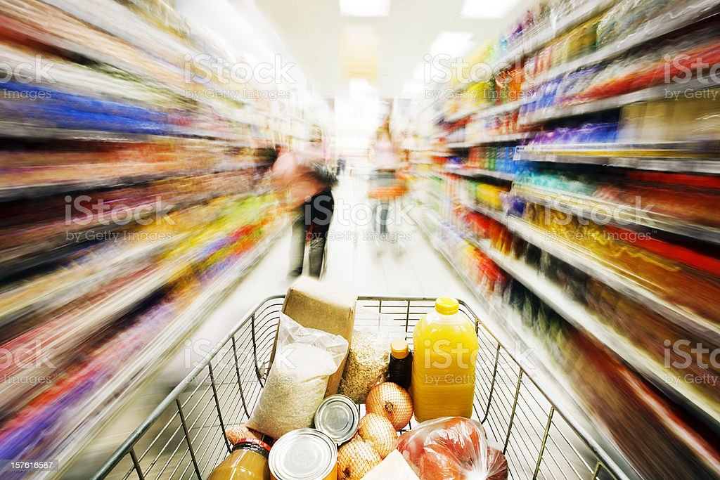 Shopping in a hurry: shelves blur as cart races past stock photo