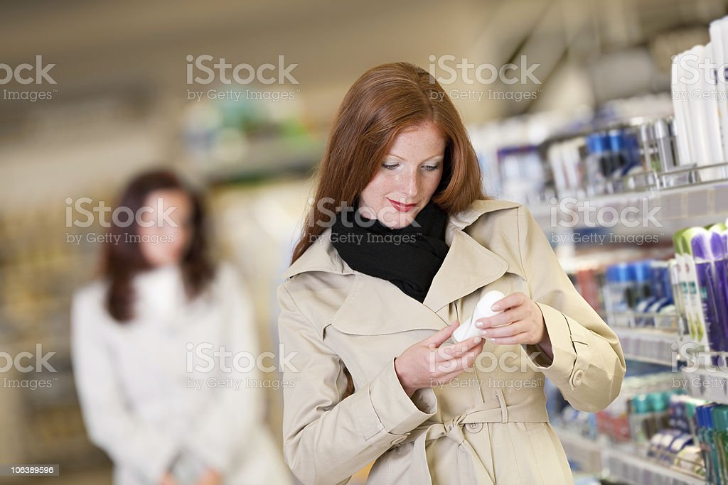 Shopping - Red hair woman buying deodorant in cosmetics department stock photo