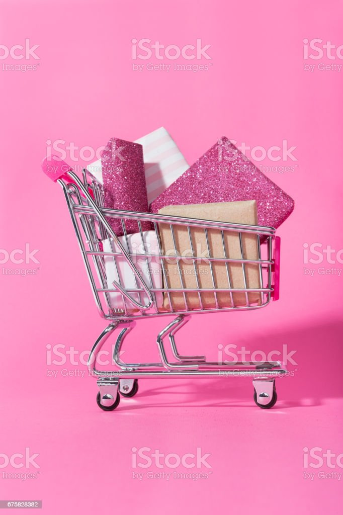 Shopping trolley full of pink wrapped gifts stock photo