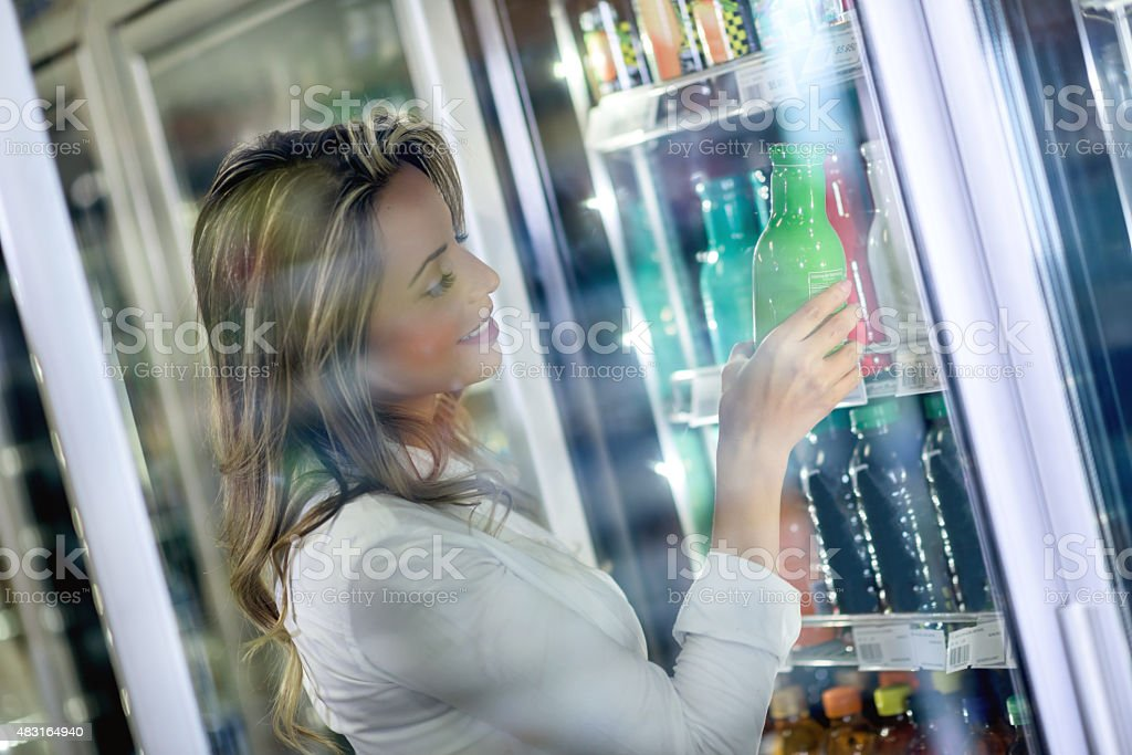 Shopping woman buying a drink at the supermarket stock photo