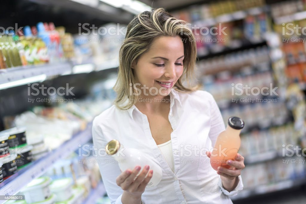 Shopping woman comparing products at the supermarket stock photo