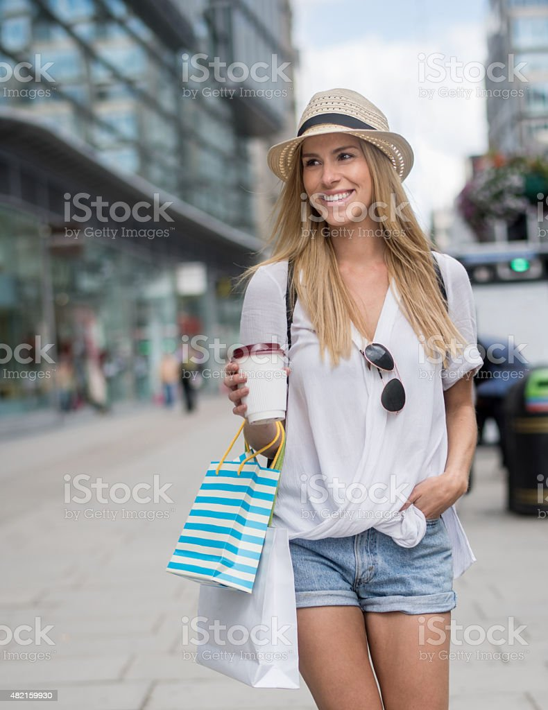 Shopping woman having a coffee on the go stock photo