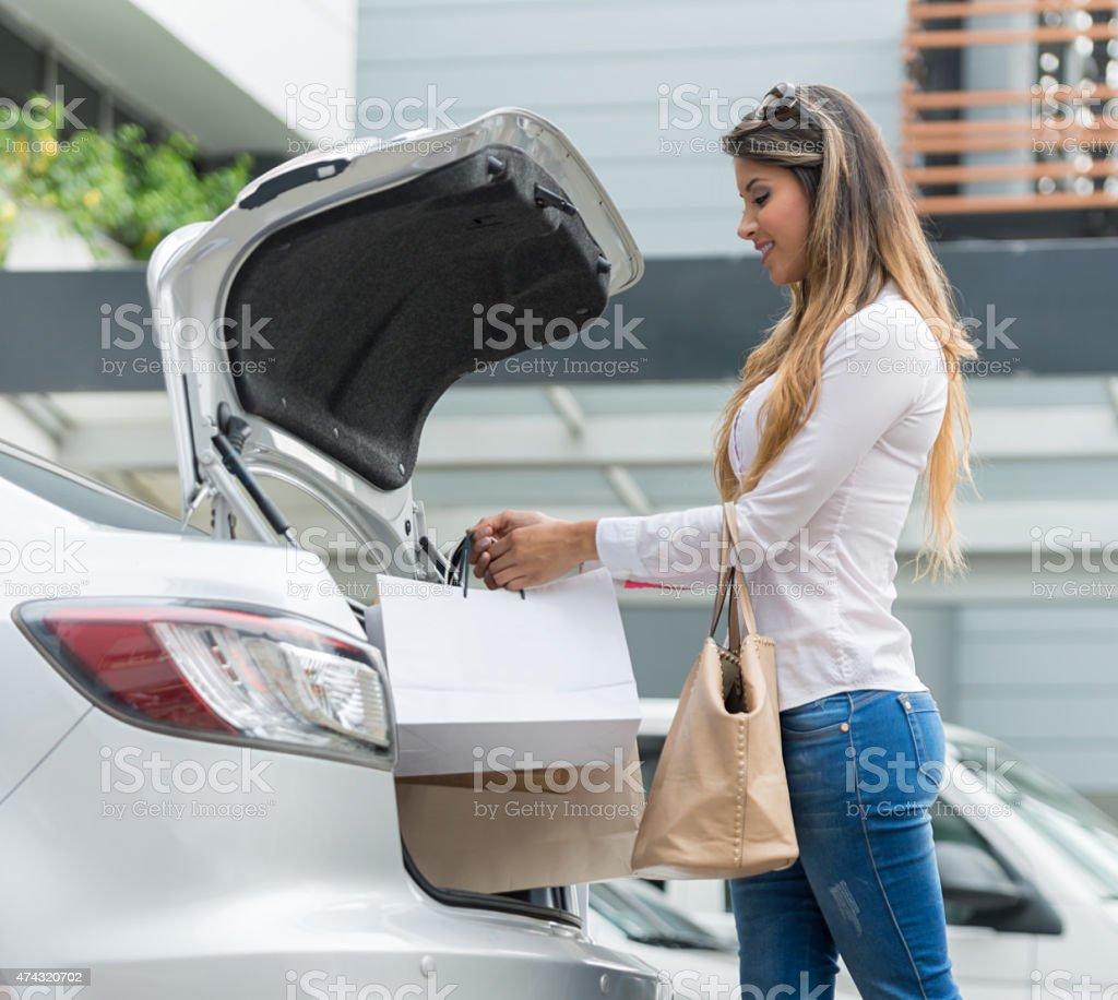 Shopping woman putting bags in the car stock photo