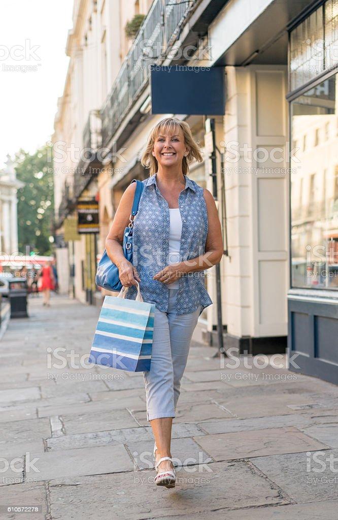 Shopping woman walking on the street stock photo