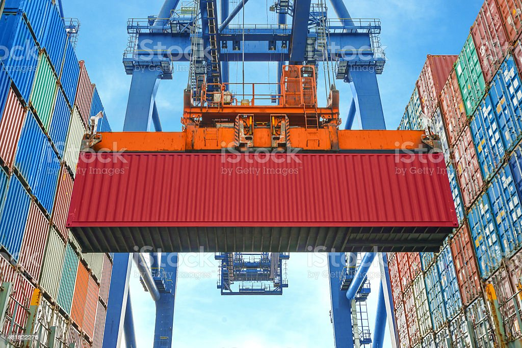 Shore crane loading containers in freight ship stock photo