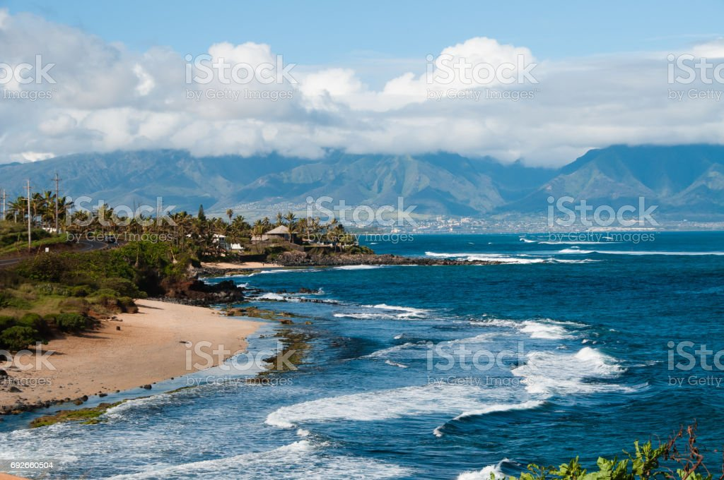 Shoreline and surf, looking back at Kahului and the cloud covered mountains from the road to Hana. stock photo