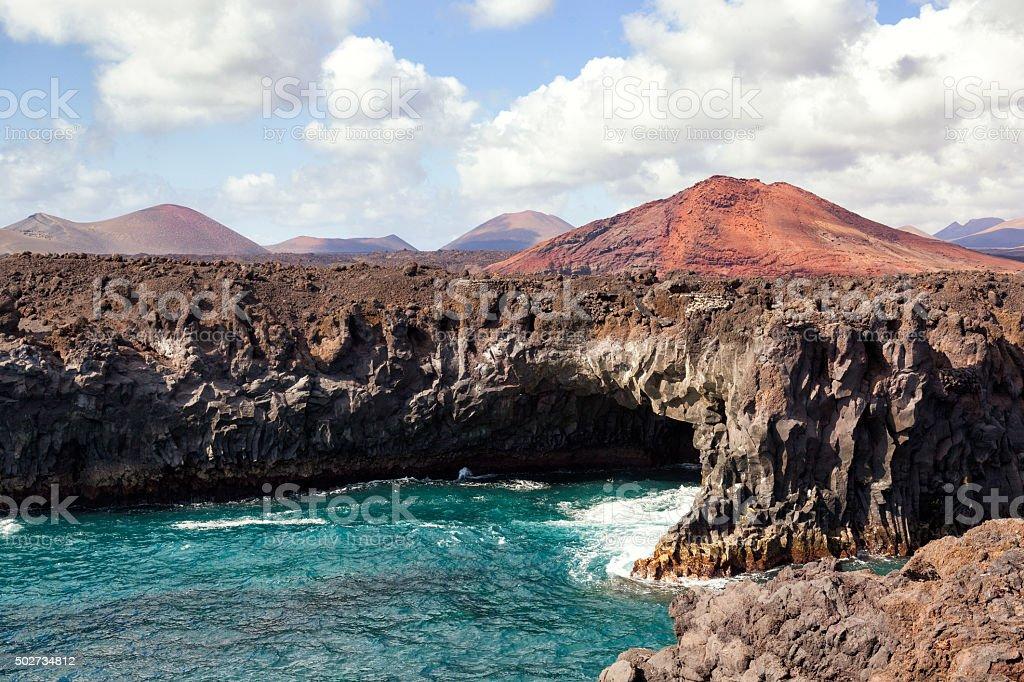 Shoreline cave and volcano stock photo