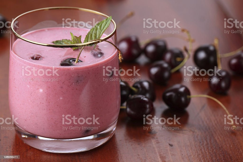 Short glass of cherry milkshake on a table with cherries stock photo