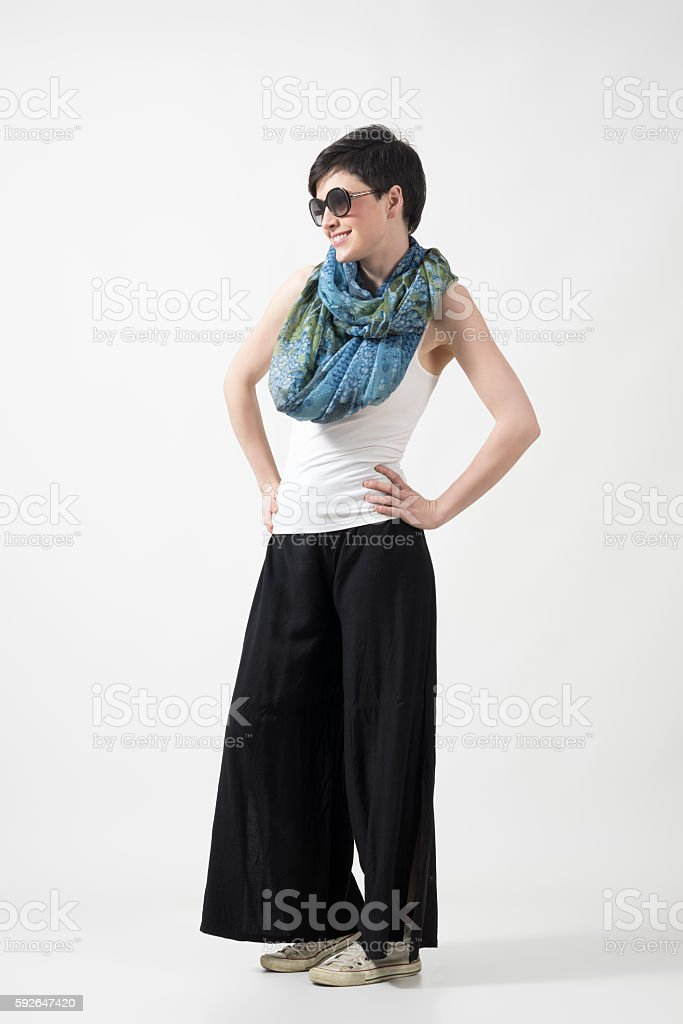 Short hair girl with sunglasses and shawl with akimbo pose stock photo