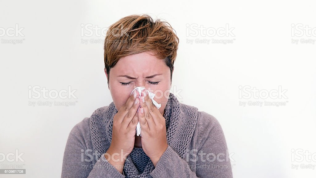 Short haired woman wearing a sweater blowing her nose stock photo