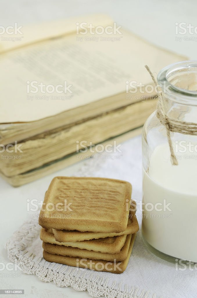 Short pastry and milk bottle on vintage doily royalty-free stock photo