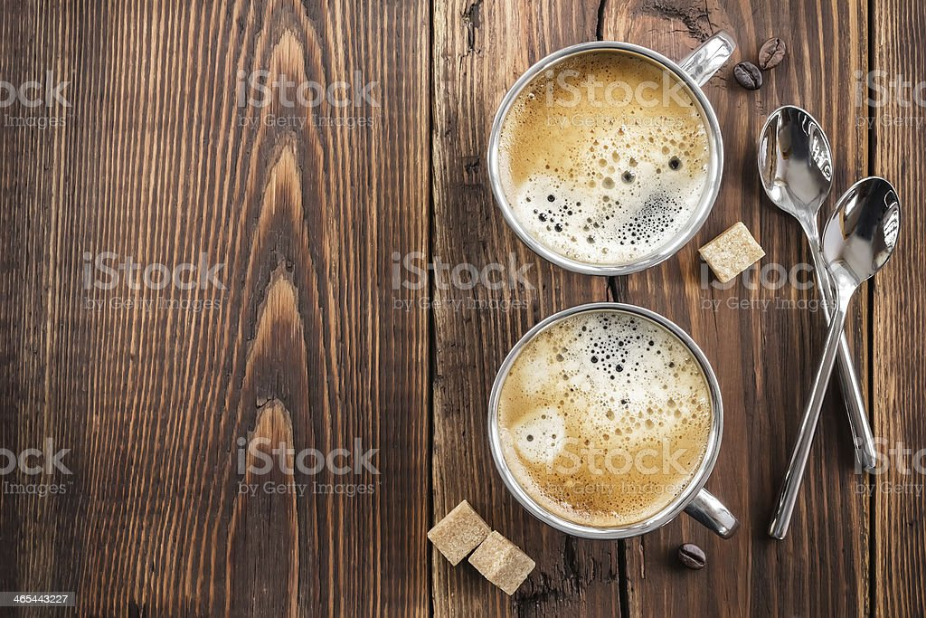 A shot from above of two cups of coffee on a wooden table stock photo