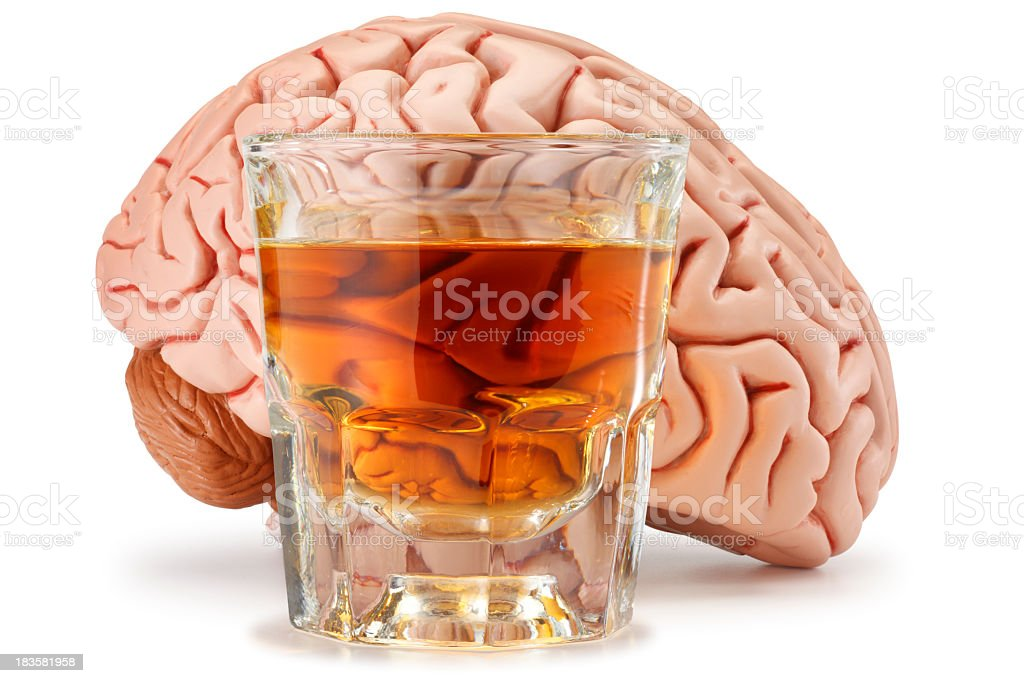 Shot glass of whiskey in front of a brain stock photo