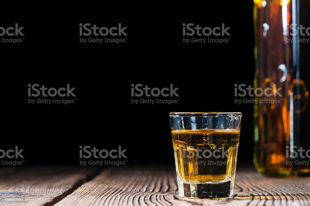 Shot glass with whisky on a wooden table fading to black stock photo