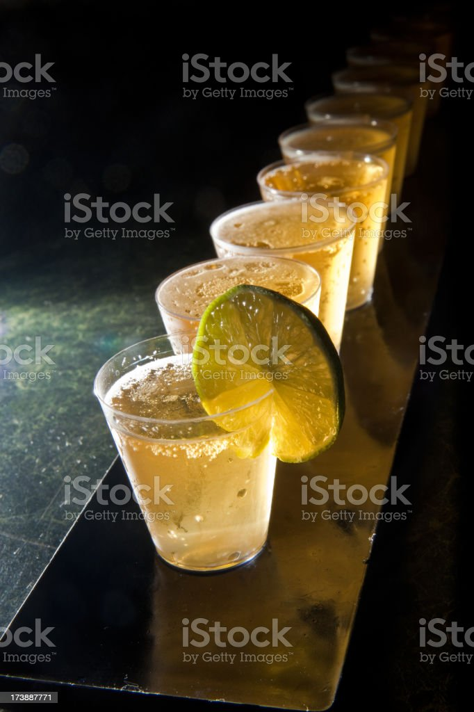 Shot glasses in a line with lime royalty-free stock photo