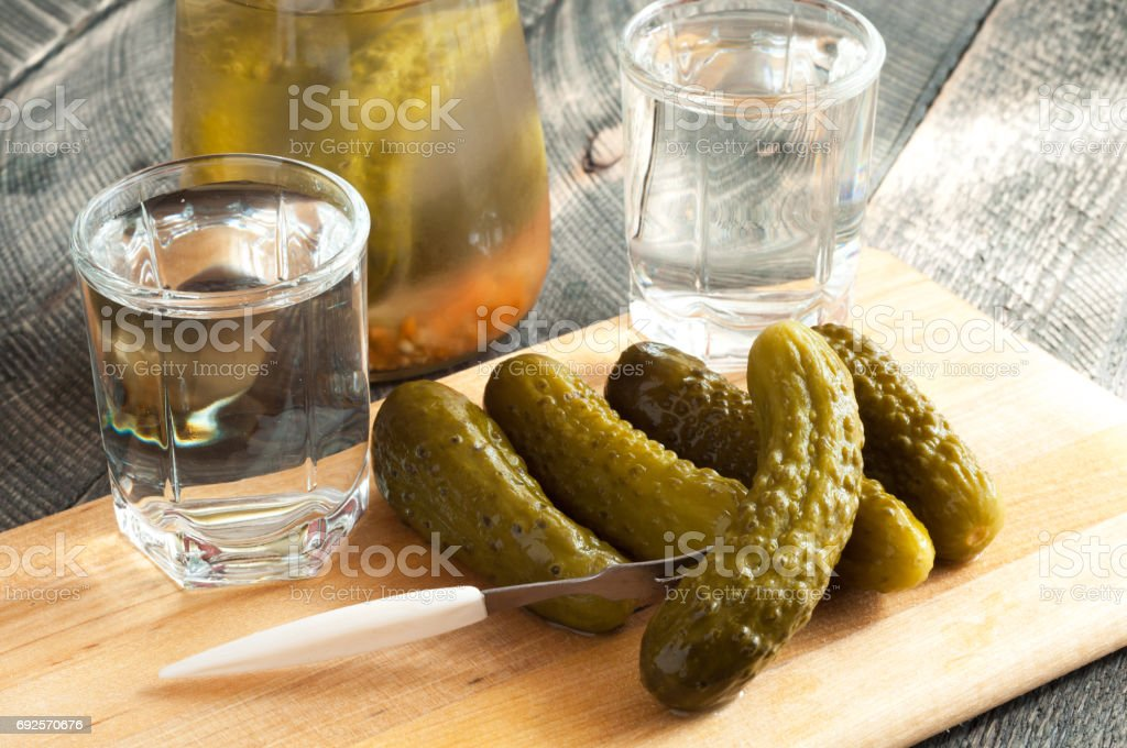 Shot glasses with vodka and pickled cucumber on a fork. Alcogol drink concept stock photo