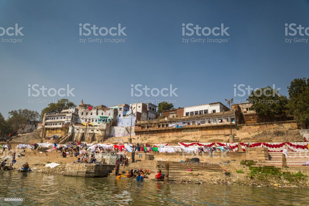 Shot in the holy Indian city of Varanasi, a view of the Ganges river and its bathers who go in the water to purify themselves, as part of Hinduism beliefs. stock photo