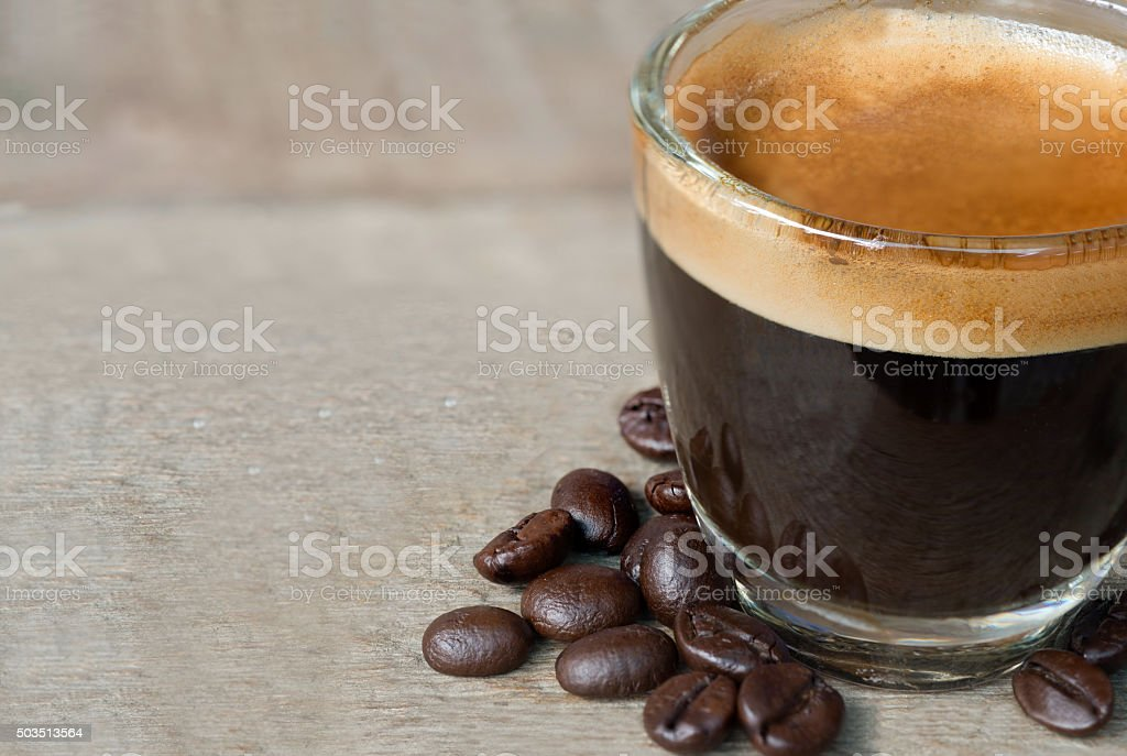 Shot of Espresso with beans on wood stock photo