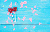 Shot of lollipops around small paper hearts