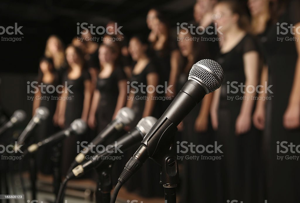 Shot of microphones with choir in the background stock photo