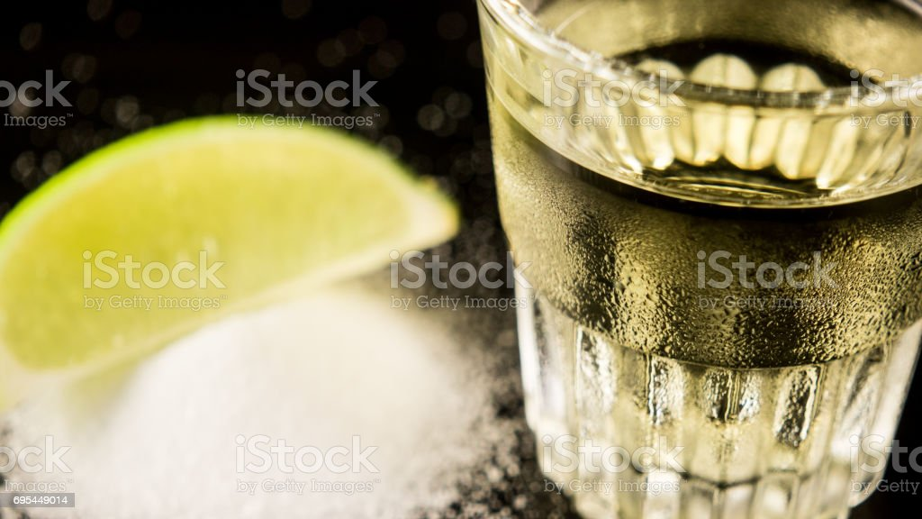 A shot of tequila on the table next to salt and lime stock photo