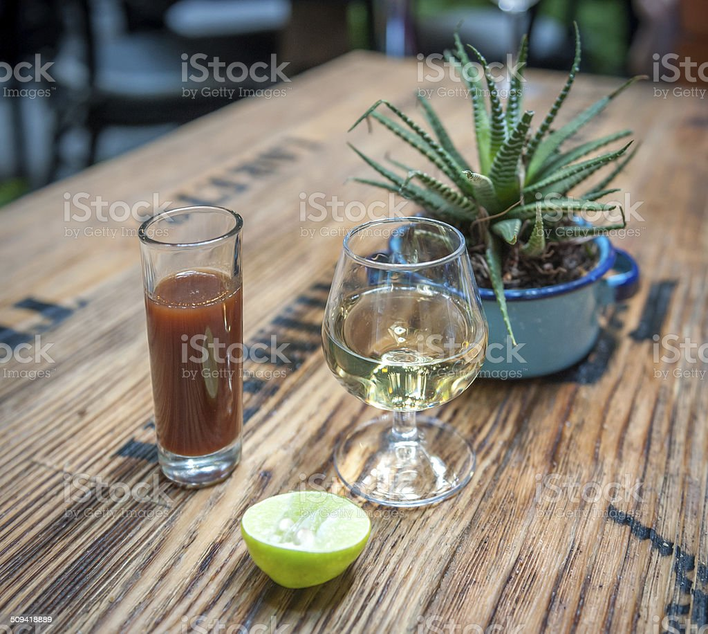 Shot of tequila, sangrita and lime - drink mexican style stock photo