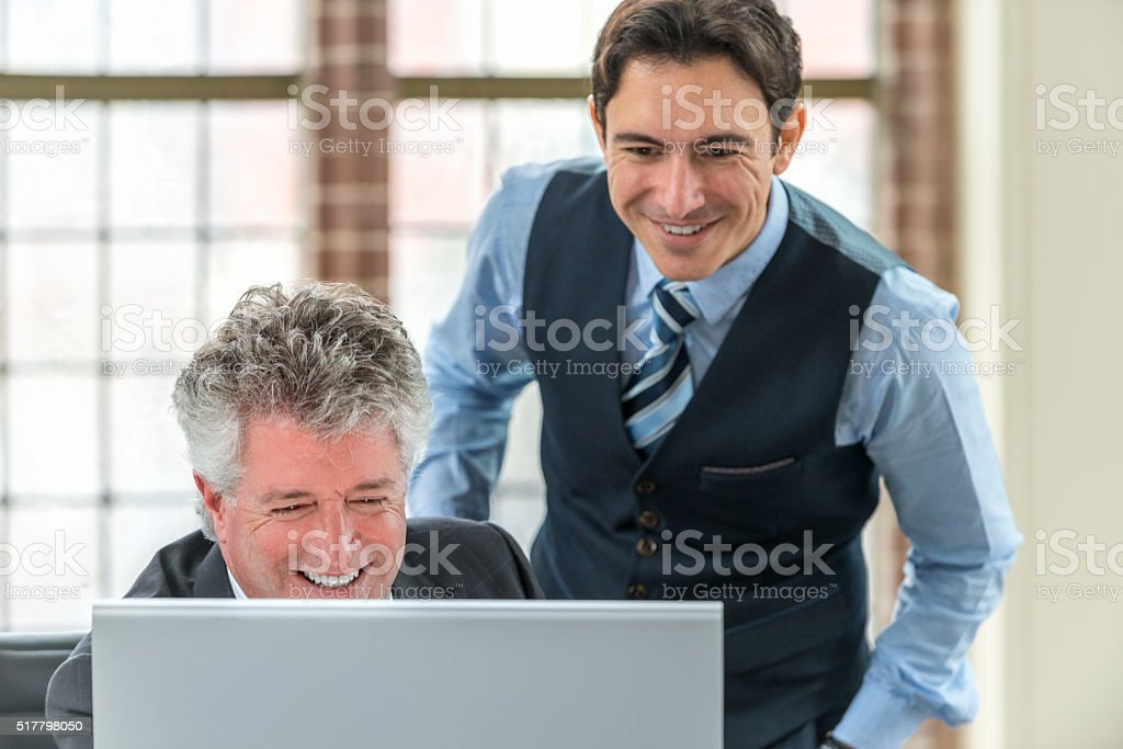 Shot of two businessman talking over a monitor stock photo