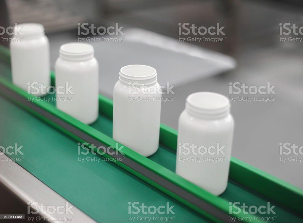 Shot of white bottles on a green conveyor stock photo