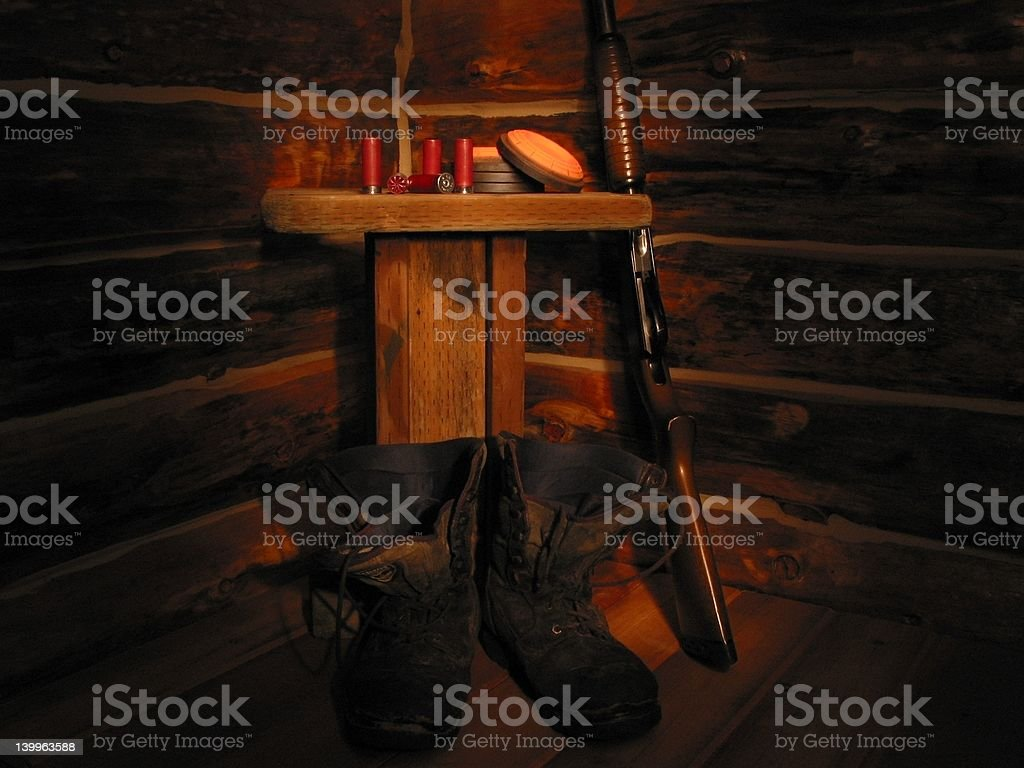 Shotgun and boots in corner of log house. stock photo