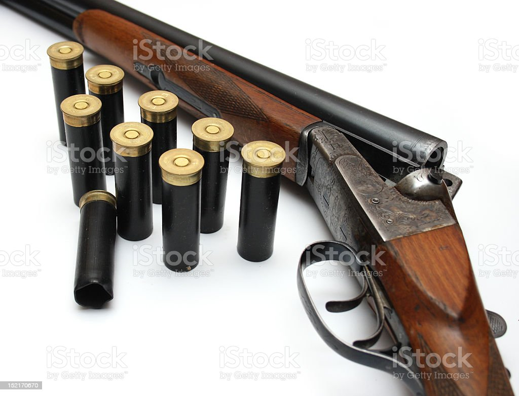 Shotgun lay on its side with 9 black bullet cartridges stock photo